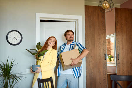 young married couple got keys from their new house, they are happy to move into new apartment, hold box and plant in hands, smile