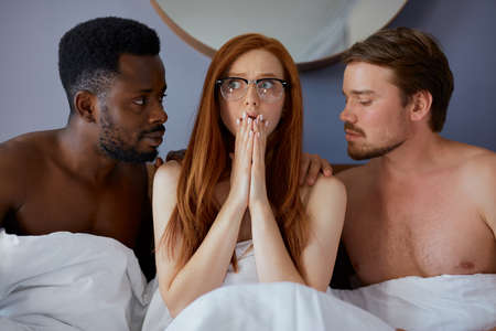 girl woke up with two diverse men, she is in shock, redhead woman does not remember with whom she spent the night with Stock Photo