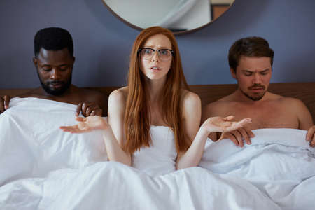 african and caucasian men lie on bed with redhead sexy woman, they want to have sex with her but they cant get it, she is in contemplation 写真素材