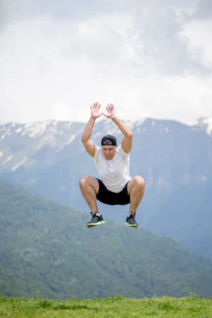Joyful caucasian man jumping in air at mountains to clouds sky Lifestyle Sport CrossFit and Travel Nature, emotional success concept adventure active vacations outdoor. 写真素材