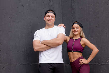 fitness, sport, friendship and lifestyle concept - Happy young athletic caucasian couple isolated against grey wall