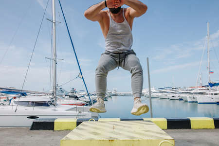 Caucasian fit athlete exercising in box jumping at pier. Fit man is performing box jumps at ship dock outdoors.