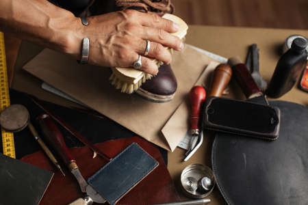 Care for leather shoes, close up shot of cropped shoemaker hands rubbing up custom made boots with a brush over work desk background