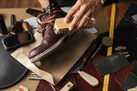 Cobbler s hands cleaning handmade shoes with a brush over his working place background, close up. Banco de Imagens