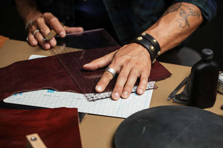 A close-up of a man skinner makes leather pattern with the help of a special knife in the workshop. Leather Craftsman manufactures a custom made pocketbook. Imagens