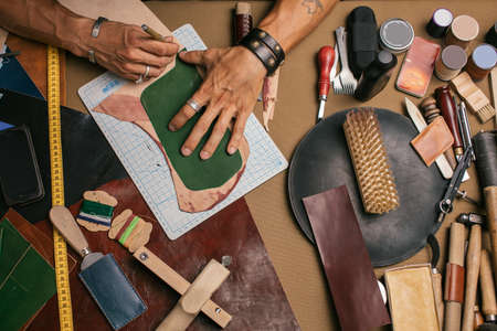High angle view of caucasian male hand master cutting with a knife pattern from genuine leather. Hand-made leather goods manufacturing. Small business concept