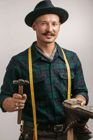 Studio isolated portrait of a caucasian shoemaker with measure tape an hammer holding custom-made leather boot over white background.