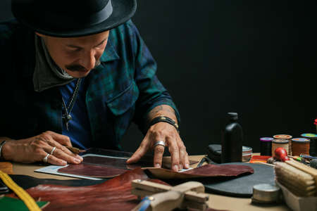 Professional shoemaker with moustache, wearing hat, working with leather at a workshop over dark background. Small Business, Leathercraft Concept Foto de archivo
