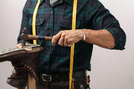 Cropped image of a shoemaker with measuring tape, working with of a shoemaker man working with leather boot using crafting hammer, isolated shot over white background