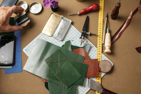 Set of leather craft tools on paper background. Workplace for shoemaker. Piece of hide and working handmade tools on a work table.