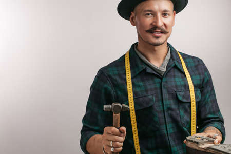 Studio portrait of smiling caucasian mid-aged cobbler wearing trendy hat with measuring tape slapping sole on man s leather boot.
