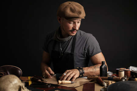 Diligent moustached cobbler wearing apron and cap engaging in shoemaking process, cutting from leather the sole of shoe. Boots and shoes manufacturing and repair micro-entrepreneur Concept
