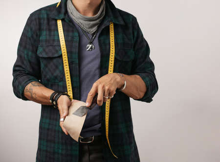 Cropped image of a shoemaker with measure tape and cobbler s tools isolated over grey studio background with copyspace. Small Business and Handycraft