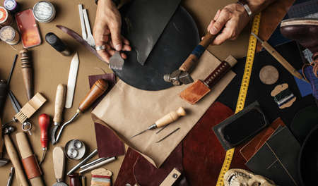 Close up of leather designer hands making custom made shoes working with genuine leather and hammer at a workshop. Foto de archivo