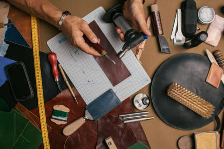 Close-up of male master cutting piece of leather with crafting tools for future wallet at workshop. High angle view of cobbler working place.
