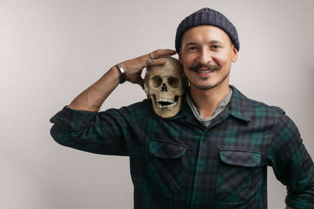 Positive with mustache, wearing knitted hat and shirt, and holding human scull with funny joking look as if he poses with his friend in studio against white background