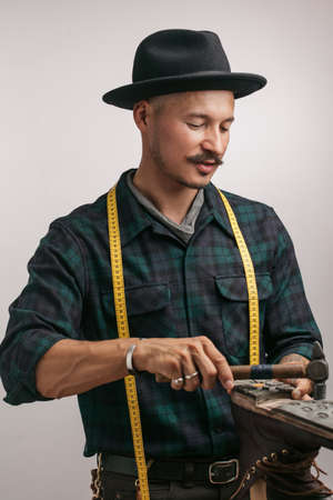 Professional shoemaker in studio. Unrecognizable shoemaker performs shoes in the studio craft