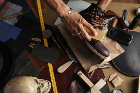 Close up male hands taking care for self made luxury leather shoes in bootmaker workshop.