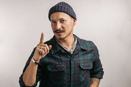 Confident positive man in knitted hat and casual shirt looking at camera pointing finger upwards. Фото со стока