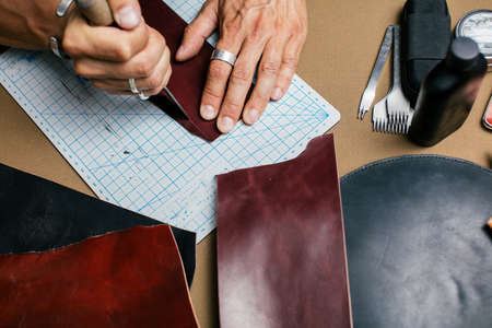 Cropped image of a male shoemaker making design for a new shoes at his workshop. Genuine leather handbag master at work in local workshop. Handmade concept. Foto de archivo