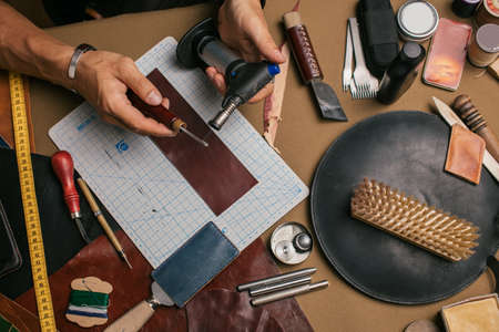 A close-up of a man skinner makes leather pattern with the help of a special knife in the workshop. Leather Craftsman manufactures a custom made pocketbook. Foto de archivo