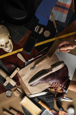 Shoe or belt maker working place at leather workshop with cobbler s and craft tools on background Foto de archivo