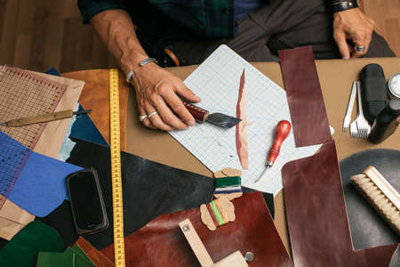 Detailed process of leather goods craftsman making custom made wallet from genuine leather at workshop. Handmade concept. Leather craft. Small business, craftspersons and micro-entrepreneurs Concept
