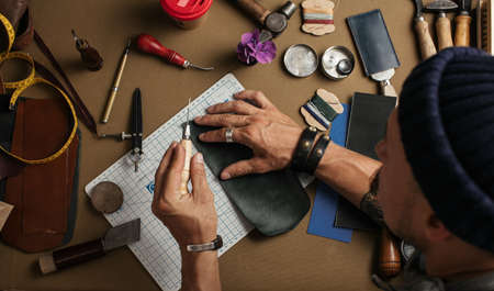 Close-up of skilled leather craftsman creating workpiece made for individual order. Leather Bags and Shoes Craft Industry and Equipment. Small business Foto de archivo