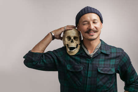 Stylish happy man with mustache and knitted hat, holding scull while posing indoors, with copy space for your text or promotional content Фото со стока