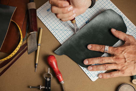 Working process of hand made leather wallet production in the leather workshop. Male hands close up holding crafting tool and working with leather. Banque d'images