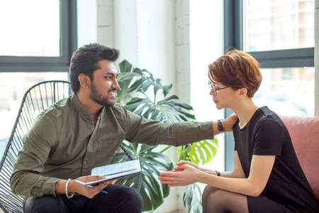 Therapist cheering up his extremely depressed patient in modern room Standard-Bild