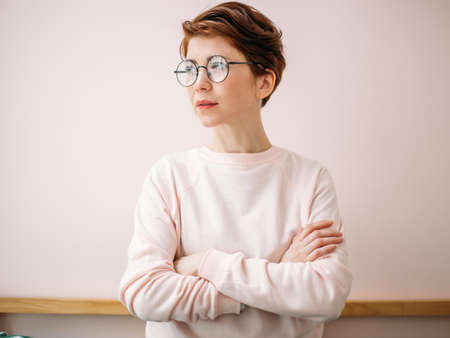 Portrait of woman wearing eyeglasses on pink background in home