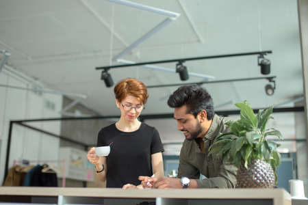 Two business people discuss meeting at table with documents and write notes