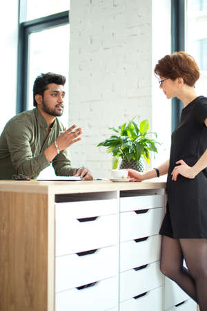 business woman and business man talking about deals at meeting in modern office and sign documents or writing notes