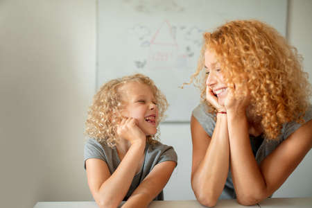 Beautiful Mother with gorgeous curly hair and her daughter, being the image of her mother, smiling and looking at each other with love at hapyness. Family relations concept. Motherhood.