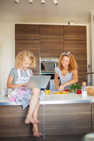 Little girl, daughter sitting on table, using laptop and earphones, looking at screen, watching cartoons, playing video game while mom cooking, family spending time together