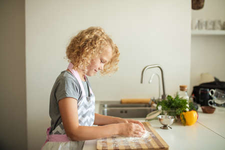 Little cooker at work. Fair haired six years old girl kneads the dough from flour standing at the kitchen table