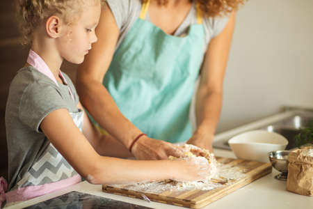 Close up of grown up and child s female hands kneading dough at home, Homemade food concept.