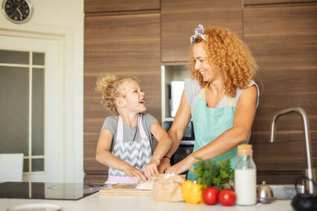 Beautiful blond mom showing her daughter the process of making cookies at the kitchen. Female parent engaging in everyday doings together with child. Family at home lifestyle photo.