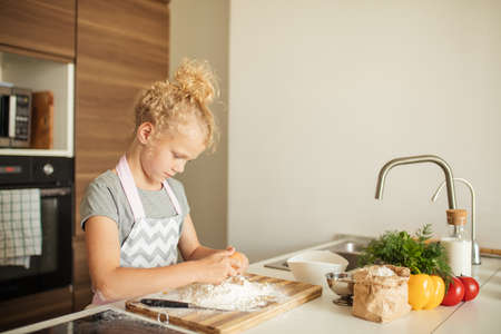 Busy little girl with blonde hair, dressed in apron cracking egg into a flour pile while baking at well lit white kitchen background.