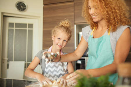 Cute little girl and her beautiful mother, both with blonde curly hair pouring olive oil into the bowl and smiling while preparing dough for baking. Standard-Bild - 152817001