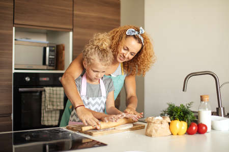 Beautiful young mom and her little daughter with funny curls rolling dough for cookies with rolling pin and smiling while baking in kitchen at home