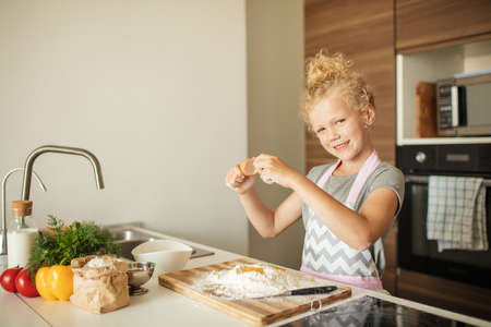 Cute little girl with blonde hair, dressed in apron cracking egg into a wooden bowl and smiling at camera while baking in kitchen at home