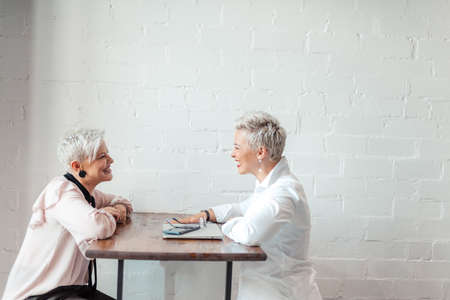 Two women working together at meeting in cafe, talking, smiling and drink coffee