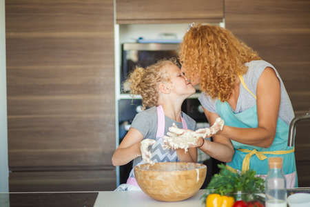 Cooking with mother may be so funny. Attractive young caucasian woman and her 7 years old daughter preparing on home kitchen. Having fun together while making Christmas cake. Family, kids and parents