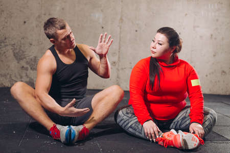young active pleasant personal trainer talking with his client while doing sport. fitness concept