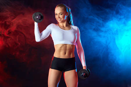 positive blonde fitness woman lifting dumbbell weights at gym. close up photo. studio shot.