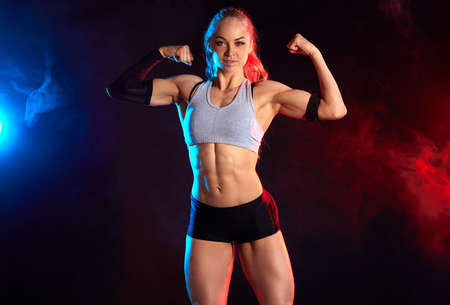 strong cheerful female bodybuilder with ponytail showing her perfect, ideal body and looking at the camera. close up photo. 免版税图像