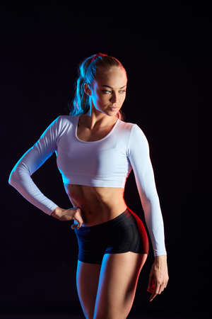 strong muscular female bodybuilder in stylish sportswear posing to the camera. close up photo. isolated black background