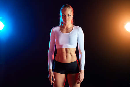 blonde dancer with ponytail looking at the camera in the fitness studio. close up photo. isolated black background with red and blue lamps.lifestyle concept 版權商用圖片